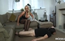 Mistress Lucy Zara in latex kicking her slave in the nuts